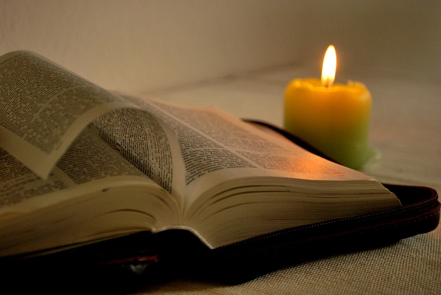Image of candle illuminating a Bible